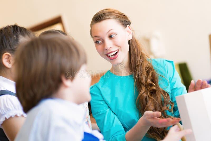 Bambini con l'insegnante impegnato nella pittura immagine stock libera da diritti