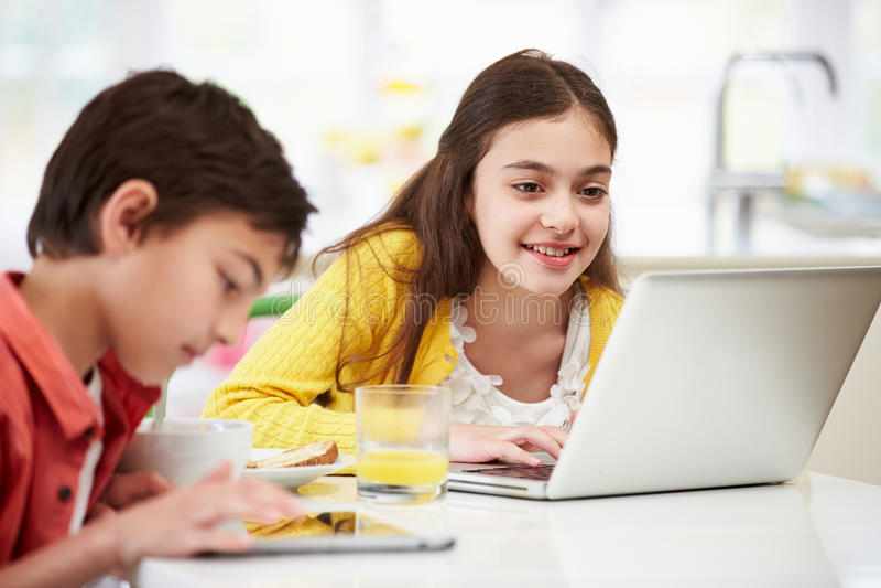 Bambini con la compressa di Digital alla prima colazione immagine stock