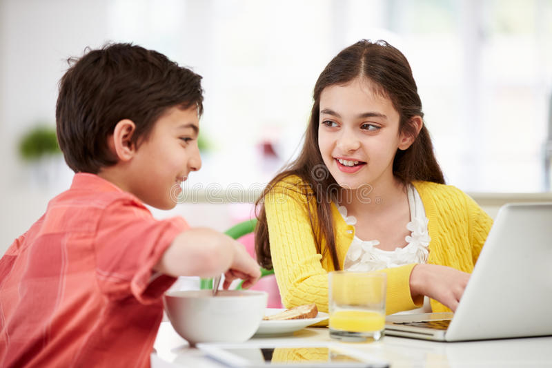 Bambini con la compressa ed il computer portatile alla prima colazione immagine stock