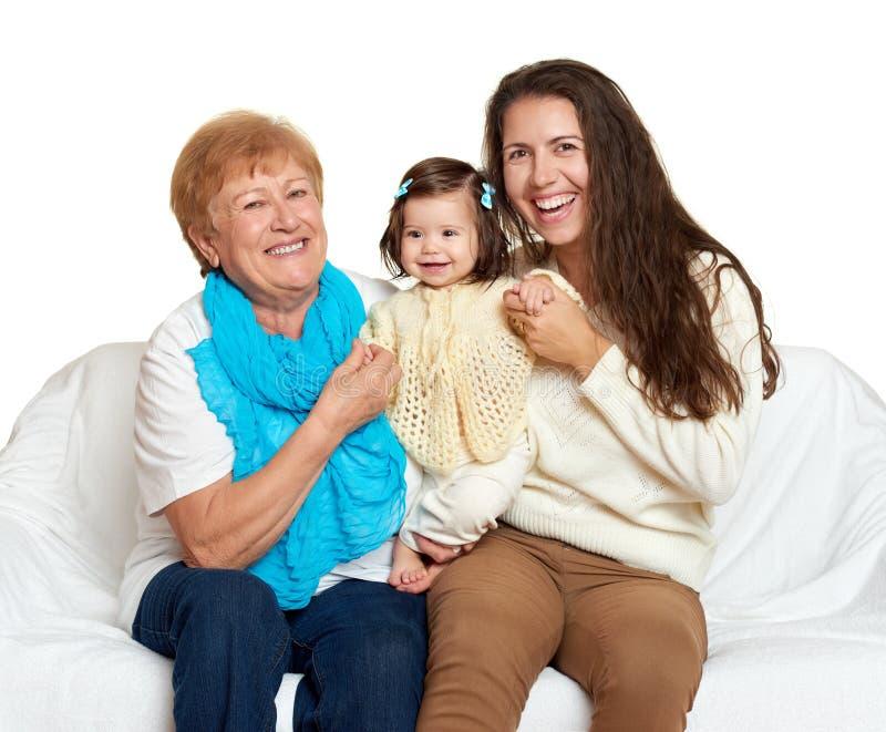 Bambini con la madre e la nonna Il ritratto della famiglia su fondo bianco, gente felice si siede sul sofà fotografia stock libera da diritti