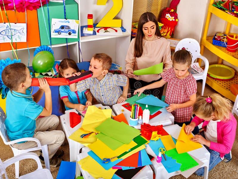 Bambini con la pittura della donna dell'insegnante sulla carta dentro immagine stock