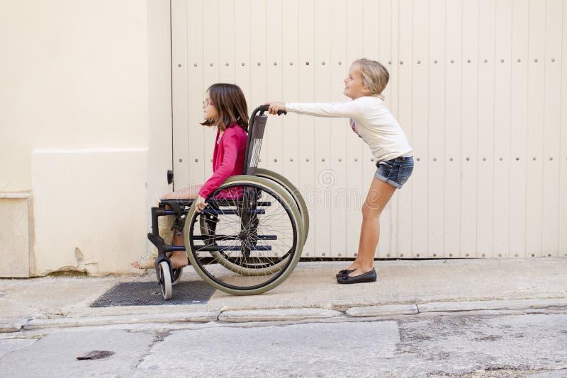 Bambini con la sedia a rotelle fotografie stock libere da diritti