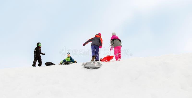Bambini con le slitte che scalano la collina della neve nell'inverno fotografia stock