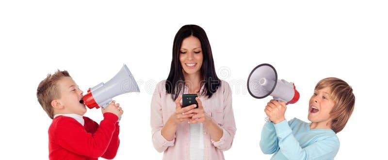 Bambini contro una ragazza del bruentte con un cellulare che grida con me immagini stock