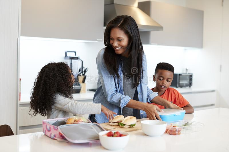 Bambini in cucina a casa che aiuta madre a fare pranzo imballato sano fotografie stock libere da diritti