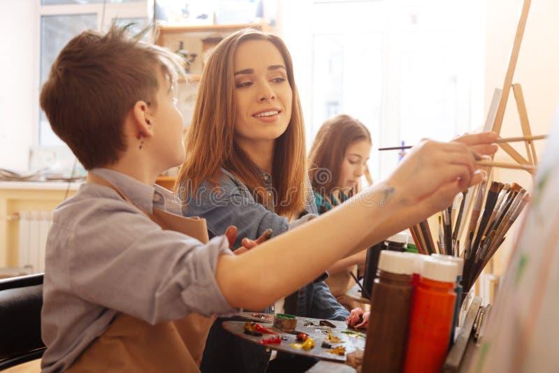 Bambini d'aiuto del giovane artista affascinante nello studio di arte fotografia stock