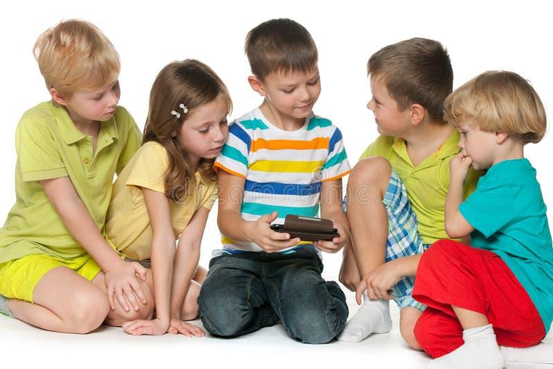Bambini del gruppo che plaing con un nuovo aggeggio fotografia stock