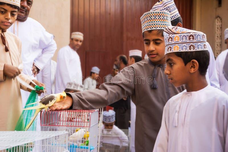 Bambini dell'Oman in vestiti tradizionali al mercato animale Oman di venerdì Nizwa fotografie stock