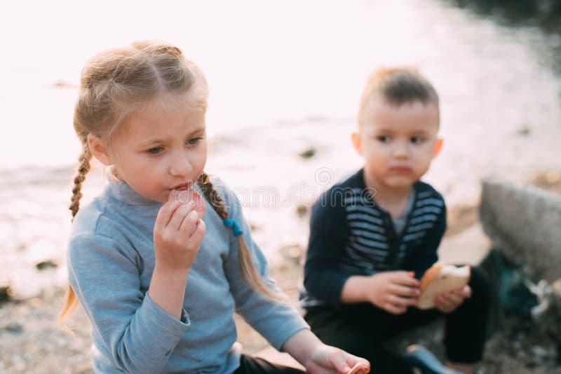Bambini della ragazza del mare che mangia il ragazzo del pane e della salsiccia immagine stock