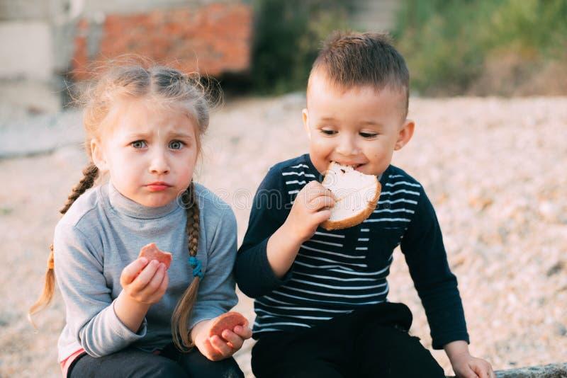 Bambini della ragazza del mare che mangia il ragazzo del pane e della salsiccia fotografia stock libera da diritti