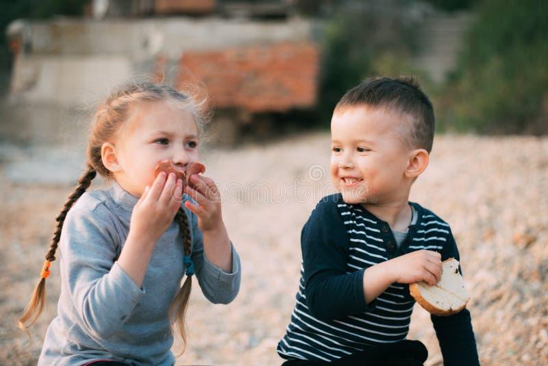 Bambini della ragazza del mare che mangia il ragazzo del pane e della salsiccia fotografie stock libere da diritti