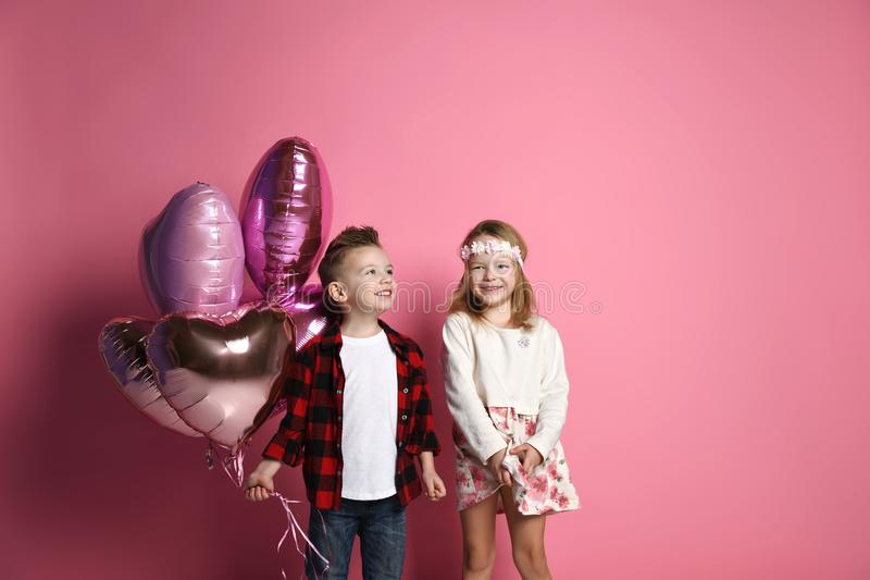 Bambini della ragazza e del ragazzino con i palloni di colore pastello per il giorno o il compleanno di biglietti di S. Valentino immagine stock