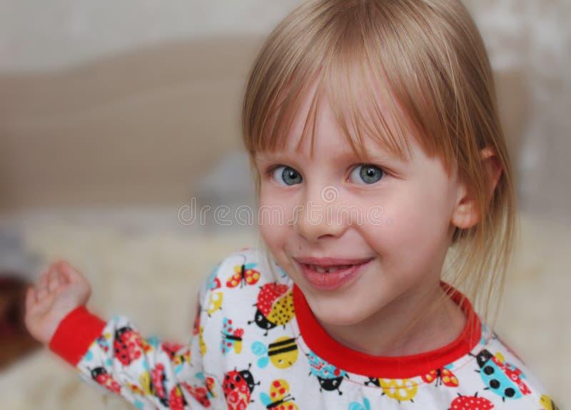 Bambini della ragazza sul letto in pigiami fotografia stock