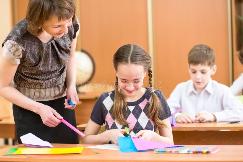 Bambini della scuola e lavoro dell'insegnante alla lezione. fotografie stock libere da diritti
