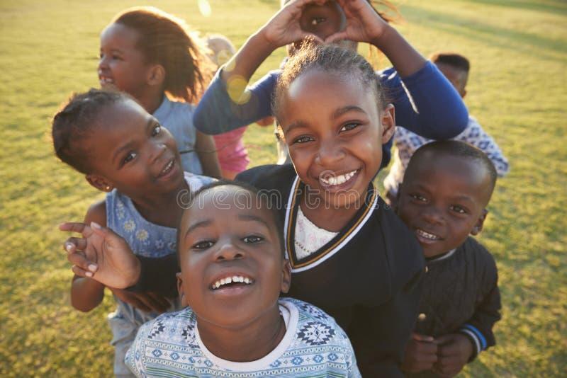 Bambini della scuola elementare divertendosi all'aperto, angolo alto immagine stock