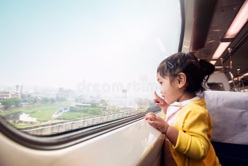 Bambini di Ecxited e felici che viaggiano in treno Una ragazza di due anni immagine stock