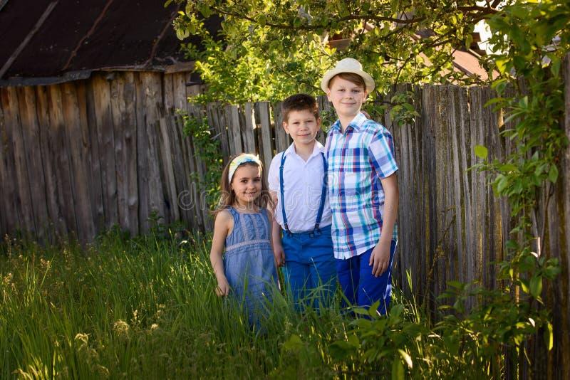 Bambini di ogni giorno caucasici nel villaggio Un ritratto di tre bambini insieme di estate immagini stock