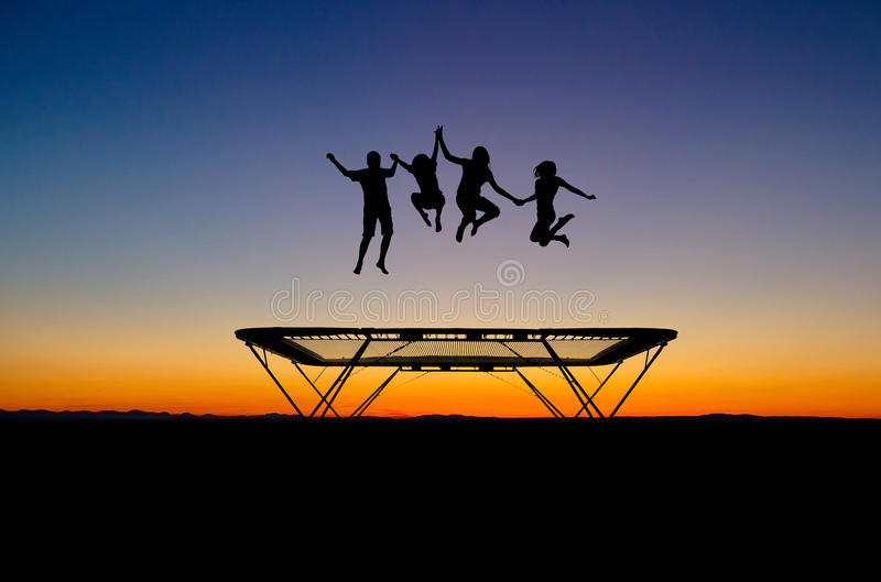 Bambini di tramonto sul trampolino fotografia stock