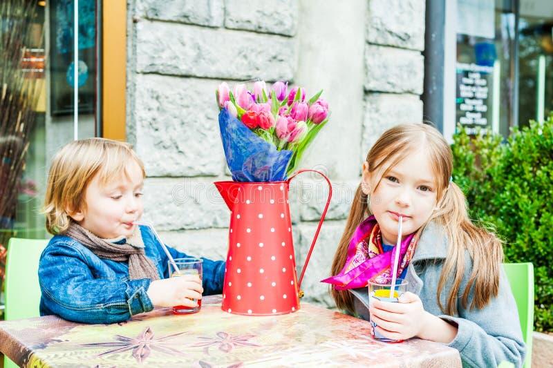 Bambini divertendosi all'aperto, riposando in un caffè immagine stock