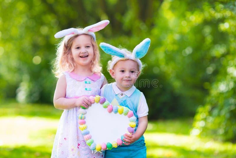 Bambini divertendosi sulla caccia dell'uovo di Pasqua immagine stock libera da diritti