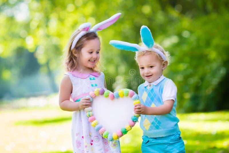 Bambini divertendosi sulla caccia dell'uovo di Pasqua fotografia stock