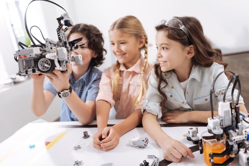 Bambini divertenti che esplorano le tecnologie moderne alla scuola fotografia stock