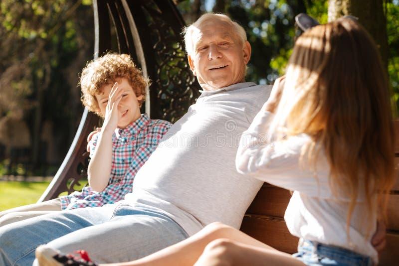 Bambini divertenti che fanno i fronti mentre essendo vicino al loro nonno fotografie stock