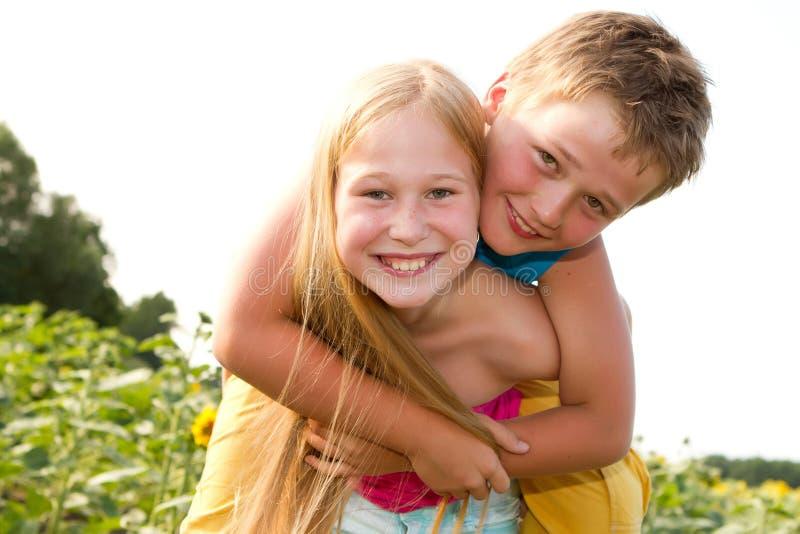 Bambini dolci nel giacimento del girasole fotografie stock libere da diritti