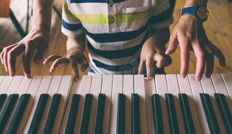 Bambini e le mani delle donne sulle chiavi del piano fotografia stock
