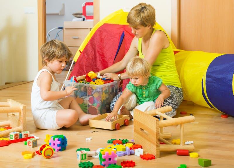 Bambini e madre che raccolgono i giocattoli fotografia stock