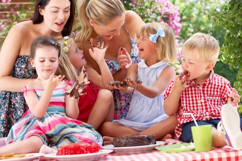 Bambini e madri che mangiano torta a Outd fotografia stock libera da diritti