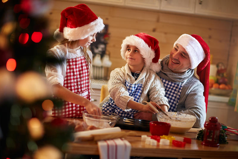 Bambini e padre che producono i biscotti di Natale fotografie stock