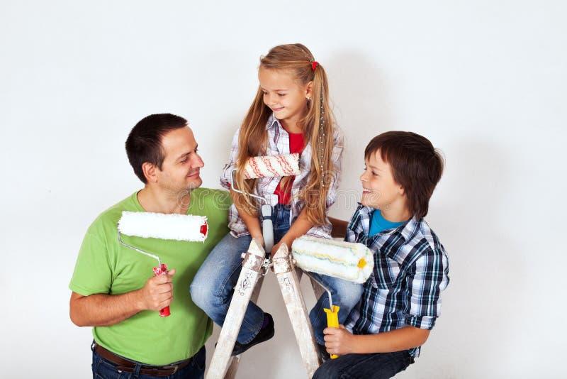 Bambini e padre con i rulli di pittura fotografia stock