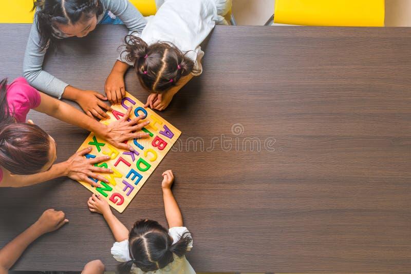 Bambini ed insegnante che giocano sulla tavola fotografia stock
