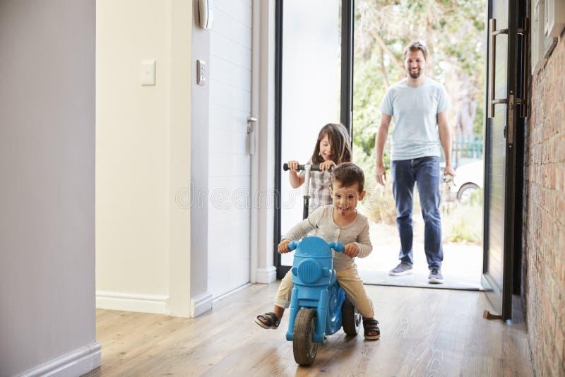 Bambini emozionanti che arrivano a casa con il padre fotografie stock libere da diritti
