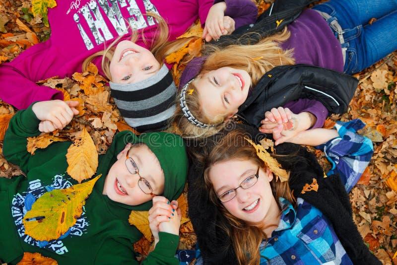 Bambini esterni sui fogli di autunno fotografie stock libere da diritti
