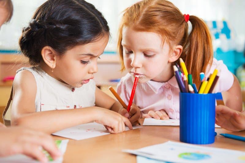 Bambini in età prescolare svegli che disegnano con le matite variopinte fotografia stock libera da diritti
