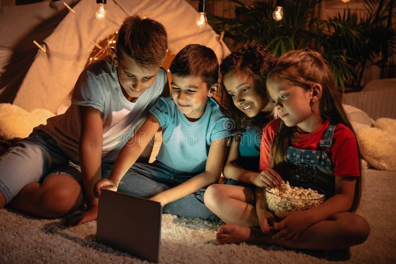 Bambini facendo uso della compressa digitale mentre spendendo tempo insieme a casa immagini stock
