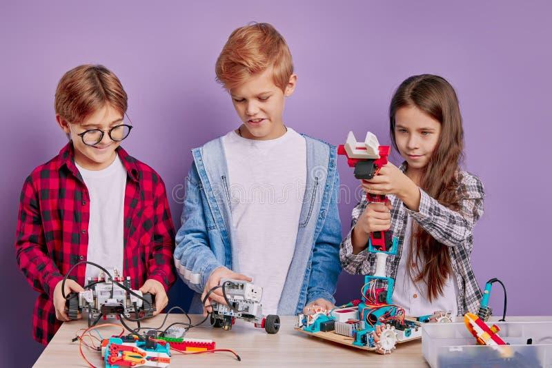 Bambini fantastici e di talento appassionati di robotica e ingegneria immagini stock libere da diritti