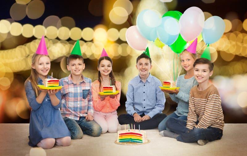 Bambini felici in cappelli del partito con la torta di compleanno immagini stock libere da diritti