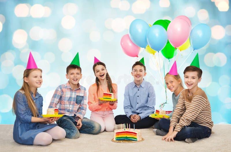 Bambini felici in cappelli del partito con la torta di compleanno fotografia stock libera da diritti