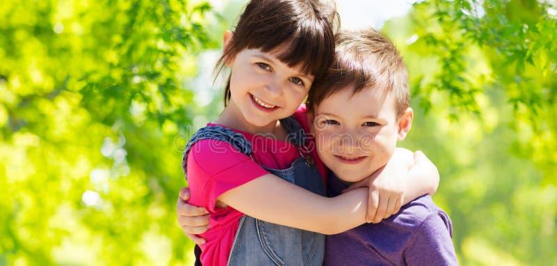 Bambini felici che abbracciano sopra lo sfondo naturale verde fotografie stock libere da diritti