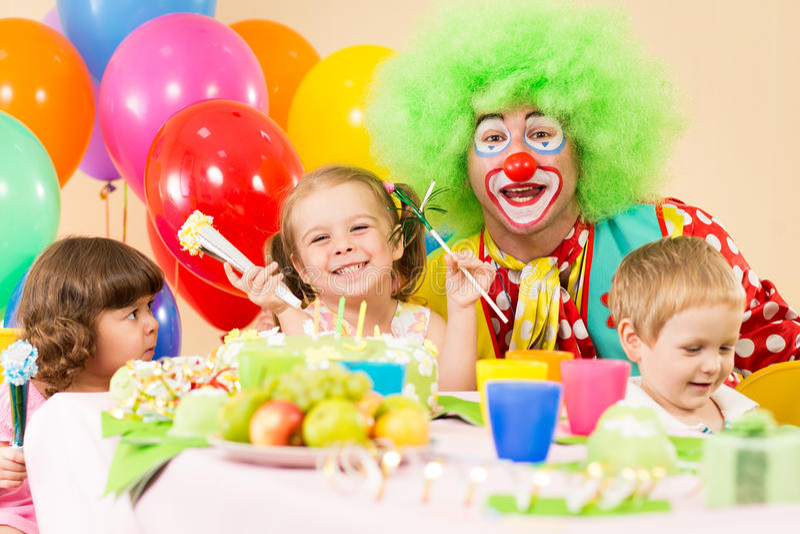 Bambini felici che celebrano la festa di compleanno con il pagliaccio immagine stock libera da diritti