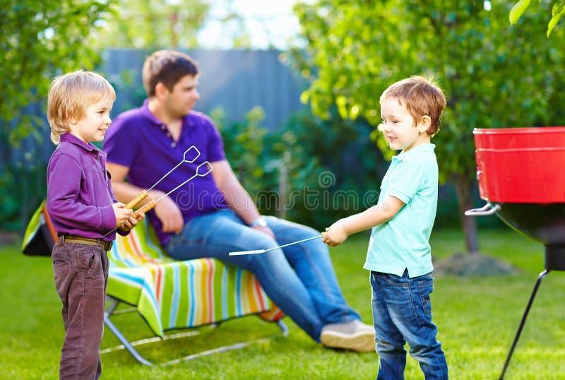 Bambini felici che combattono con gli elementi della cucina sul picnic fotografie stock