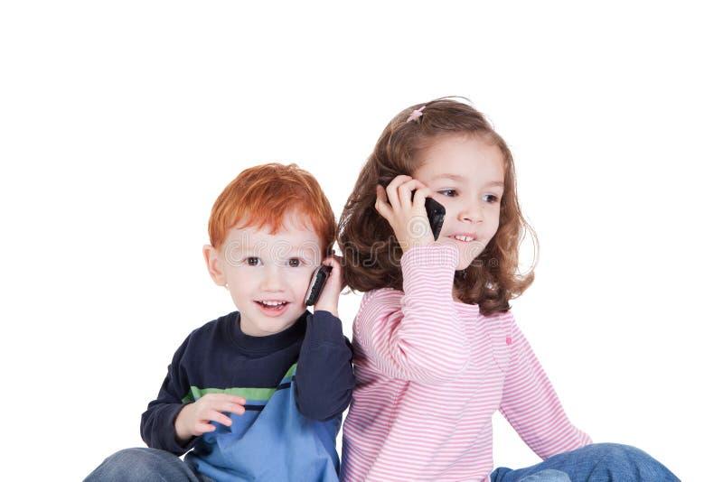 Bambini felici che comunicano sui telefoni mobili immagini stock
