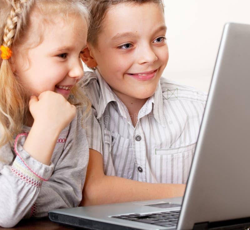 Bambini felici che giocano computer portatile nel paese fotografia stock libera da diritti