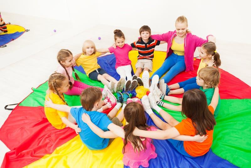 Bambini felici che giocano i giochi del cerchio con l'insegnante fotografia stock