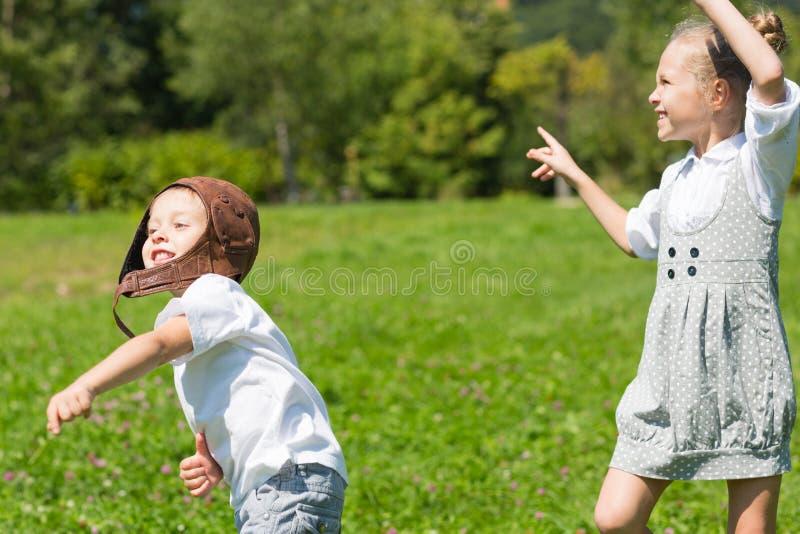Bambini felici che giocano nell'aereo di carta fotografie stock