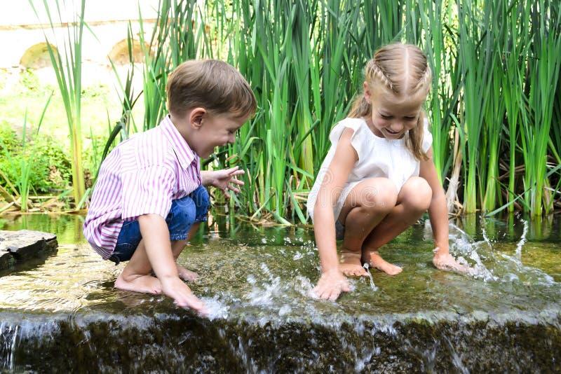 Bambini felici che giocano sull'estate calda con acqua nel parco fotografie stock