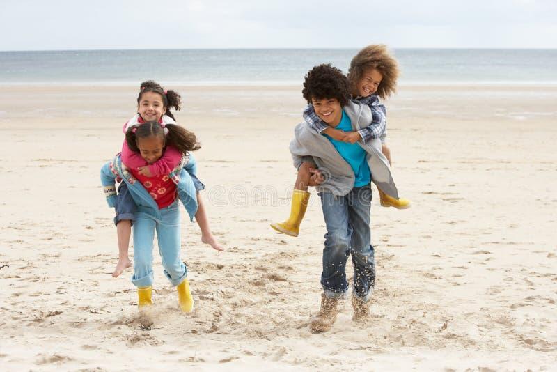 Bambini felici che giocano sulle spalle sulla spiaggia immagini stock